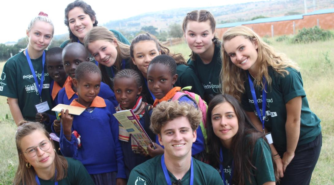 Last minute High School Special volunteers in Kenya help local children with their homework on a Childcare project.